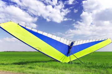 Motorized hang glider over green grass