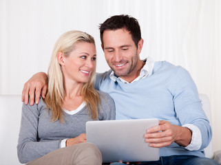 Couple looking at a tablet together