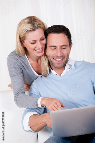 Couple laughing over information on a tablet