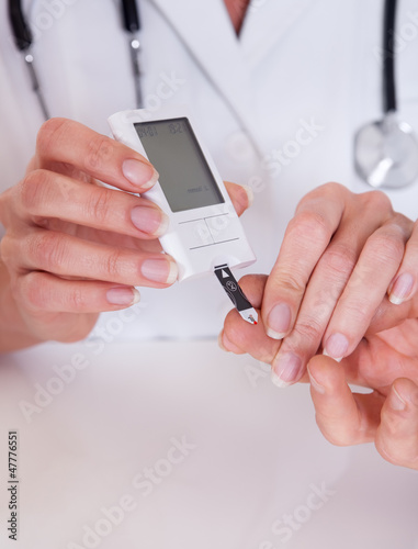 Doctor testing a patients glucose level