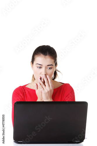 Surprised and disgusted woman working on laptop.