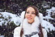beautiful brunette woman standing under snowfall