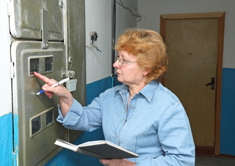 Woman takes readings of the electricity meter apartment
