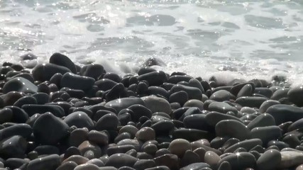 Shiny rocks at the shore of the sea reflect the sun
