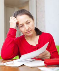 serious mature woman reads payments  at home