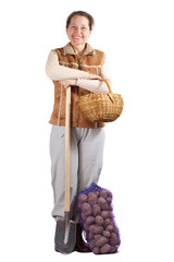 woman  with spade and harvested potatoes