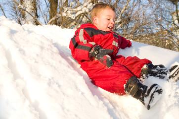 Kleiner Junge rutscht im Schnee
