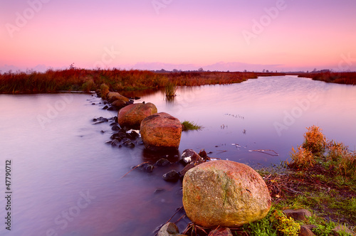 big stones on river at sunrise