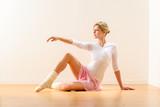 Fototapety Beautiful woman dancer practicing ballet in studio