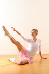 Beautiful ballet dancer lifting arm towards leg