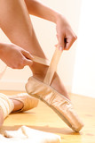 Fototapety Ballet dancer tying slippers around her ankle