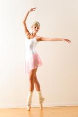 Beautiful ballet dancer practicing dance posture