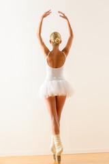 Ballerina pose from behind dancing in studio