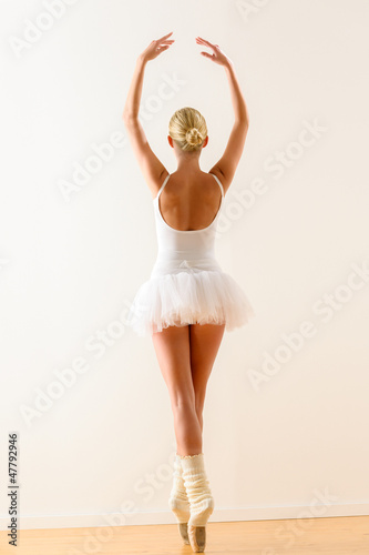 Ballerina pose from behind dancing in studio