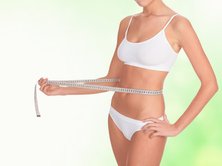 Woman taking measurements of her body, blurred background