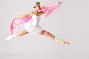 Lovely ballet dancer jumping exercising in studio