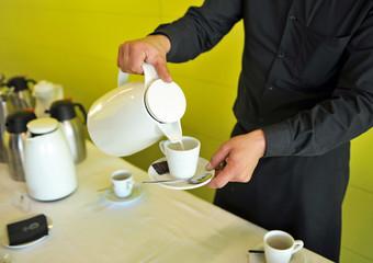 Camarero sirviendo café con leche, servicio de catering