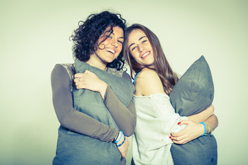 Two Beautiful Women with Pillow in the Bedroom