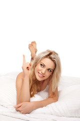 Pretty woman relaxing in bed pointing a finger