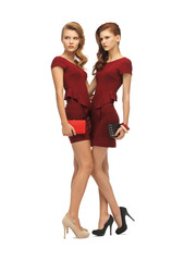 two teenage girls in red dresses with clutches