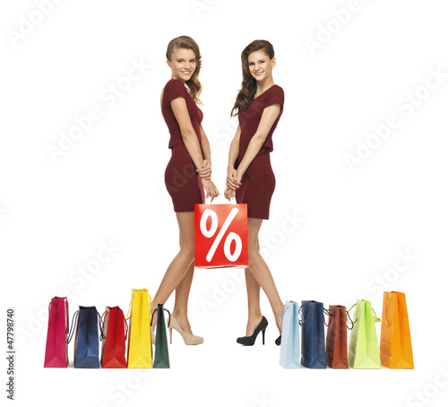 teenage girls in red dresses with shopping bags