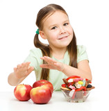 Little girl choosing between apples and sweets