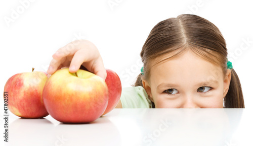 Little girl is reaching apple