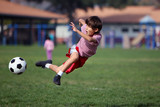 Fototapety Boy playing soccer in the park