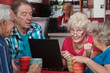 Elderly Woman with Friends and Laptop