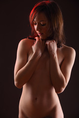 A beautiful nude woman against dramatic lighting