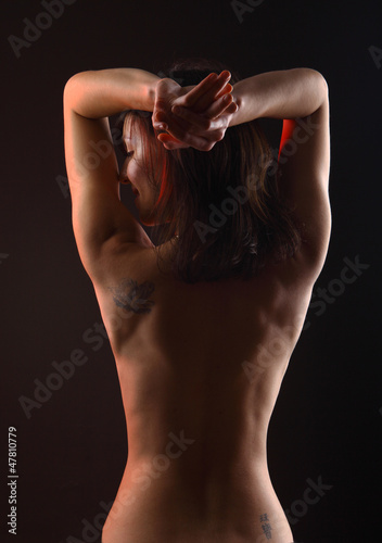 Naked woman's back against dramatic lighting