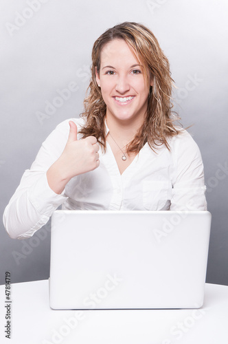 Youg woman using laptop and showing thumbs up sign