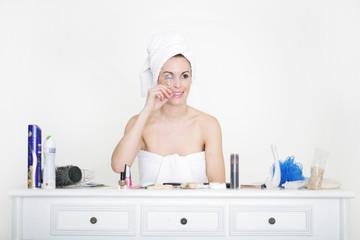Frau mit Wimpernzange im Badezimmer
