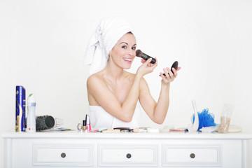 Frau schminkt sich im Badezimmer