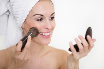 Hübsche Frau schminkt sich im Badezimmer