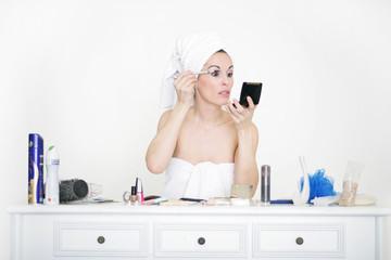 Hübsche Frau schminkt sich am Schminktisch