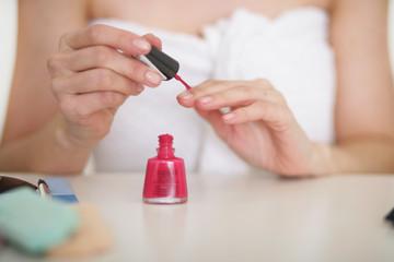 Frau beim Nägel lackieren