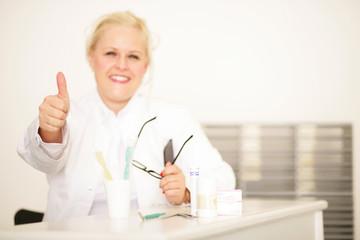 Frau zeigt Daumen hoch in Zahnarztpraxis