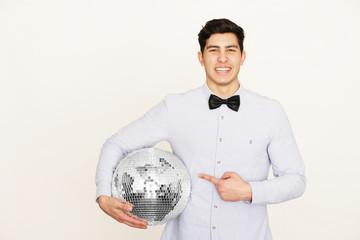 Junger Mann mit  Discokugel in der Hand