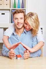 Paar hält Hände über ein Haus