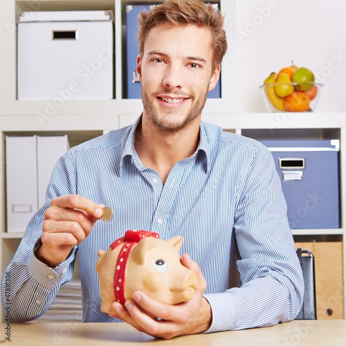 Mann spart Geld im Sparschwein