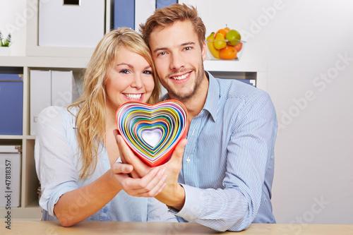 Glückliches Paar hält bunte Herzen