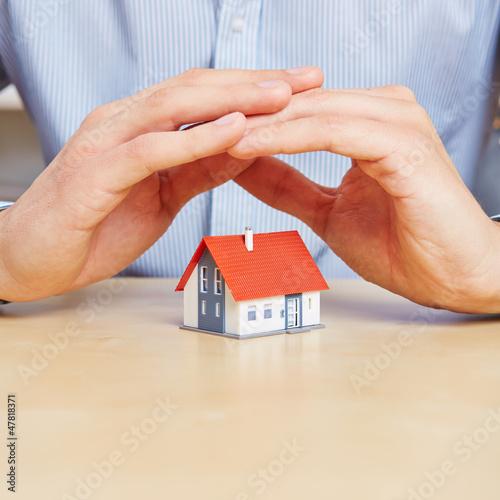 Hände schützen kleines Haus