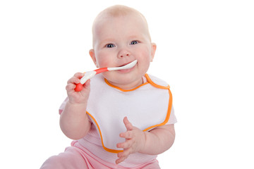 Little girl eating baby food with spoon. isolated on white