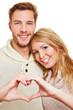 Mann und Frau bilden Herz aus Händen