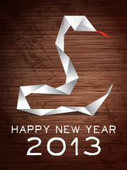 Paper snake on wooden background. 2013 year of snake.