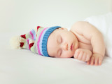 sleeping baby wearing funny striped hat