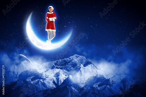 photo of santa girl sitting on the moon