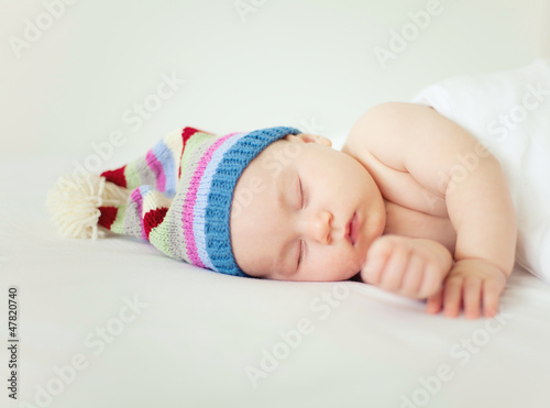 sleeping baby wearing funny striped hat Poster
