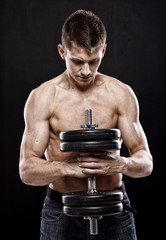 Man with naked torso holding big dumbbell